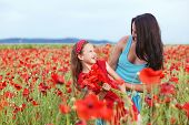 foto of 7-year-old  - Mother and her 7 years old preteen child playing in spring flower field - JPG