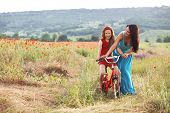 foto of preteen  - Preteen girl on bicycle with mother in spring field - JPG