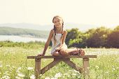 stock photo of preteen  - 8 years old preteen girl sitting on rustic bench in flower field - JPG