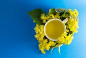 foto of lime-blossom  - Cup of tea in braided wicker basket filled with lime blossom - JPG