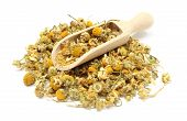 stock photo of chamomile  - Closeup of dried chamomile heap of dried chamomile on wooden spoon - JPG