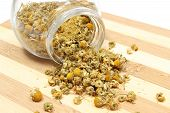 stock photo of chamomile  - Closeup of dried chamomile dried chamomile pouring out of glass jar on wooden cutting board - JPG