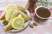 picture of baklava  - Turkish baklava and coffee on a plate with sliced lemons - JPG