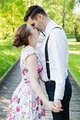 pic of suspenders  - Young couple in love holding hands and looking each other in the eyes in summer park  - JPG