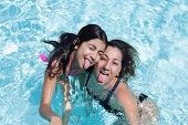 image of sticking out tongue  - Happy mother and daughter sticking their tongues out having fun in the swimming pool - JPG