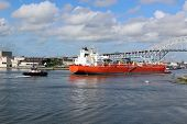 stock photo of ship  - Super tankerat entry of ship channel Coming in to pick up a load of oil from a refinery Two tug boats assisting the ship to help avoid a catastrophic accident - JPG