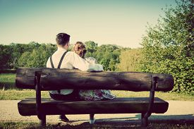 picture of sitting a bench  - Young couple in love sitting together on a bench in summer park - JPG
