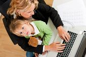 Family Business - telecommuter Businesswoman and mother is working in the internet while her daughte