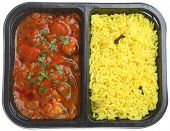 Indian chicken curry with rice in supermarket packaging tray.