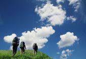 Three tourist going up along grassland