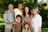 picture of extended family  - Smiling Family Looking At The Camera In The Park - JPG