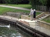 stock photo of elderly couple  - Elderly couple standing beside the lake - JPG