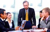 Zakenman met vier ondernemers aan directiekamer tafel op achtergrond