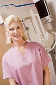 stock photo of mammogram  - Portrait Of A Nurse In Front Of A Mammogram Machine - JPG