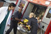 stock photo of paramedic  - Paramedics and doctor unloading patient from ambulance - JPG