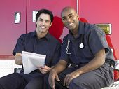 Two paramedics cheerfully doing paperwork, sitting by their ambulance