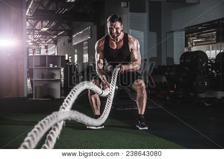 poster of Muscular Powerful Aggressive Man Working Out With Rope In Functional Training Fitness Gym