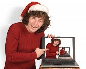 foto of santa-claus  - Young the man in cap Santa Claus with a computer on a white background - JPG