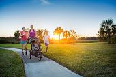 File name:Beautiful, fit young family walking and jogging together outdoors along a paved sidewalk i poster
