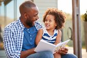 Young black father and daughter reading book outside poster