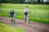 Two Kids Riding On Bikes Together On Rural Road, Outdoors poster
