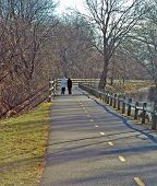 image of chafing  - Two walkers enjoy the bike path along the canal on the Blackstone River Bikeway in Lincoln RI - JPG