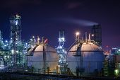 Storage Sphere Tanks In Oil And Gas Refinery Plant With Night, Glitter Lighting Of Petrochemical Pla poster