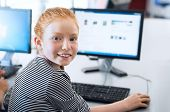 Young girl with red hair using computer at elementary school. Happy female child learning to use int poster