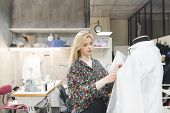 Beautiful Fashion Designer Girl Stands In A Studio Near The Mannequin And Fixes Clothes On It. Creat poster