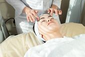 Portrait Of Blissful  Asian Woman Enjoying  Face-lifting Massage  Lying On Soft Bed In Modern Cosmet poster