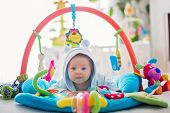 Cute Baby Boy On Colorful Gym, Playing With Hanging Toys At Home poster