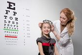 Young girl smiling while undergoing eye test with phoropter poster