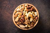 Assortment Of Nuts In Wooden Bowl On Dark Stone Table. Cashew, Hazelnuts, Walnuts, Almonds, Brazilia poster
