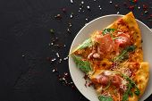 Sliced Pizza With Prosciutto And Rocket Salad On Plate, Copy Space On Black Background, Top View, Co poster