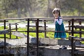 Pretty Small Blond Long Haired Girl In Nice Blue Dress Stands Alone On Old Cement Bridge Leaning On  poster