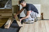 Young Handsome Professional Carpenter Installing Natural Wooden Planks On Wooden Frame Floor In Empt poster