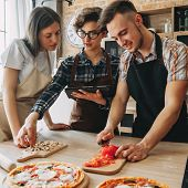 Young Woman Teach Her Friends How To Cook Food. People Cooking Pizza At Kitchen Together, Reading Re poster