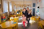 Group of four children of different ages having fun in a classroom