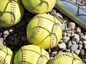 Worn Out Softballs That Have Been Relegated To Practice Time Lie Next To The Fence At The Softball D poster