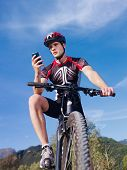 Jovem com telefone Riding Mountain Bike