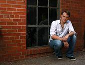 A Man Sitting By A Window