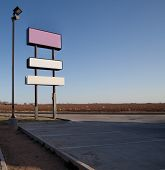 Three Blank Signs In An Empty Parking Lot
