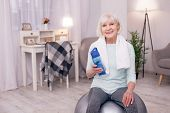 Important Hydration. Pleasant Elderly Woman Sitting On A Yoga Ball And Holding A Water Bottle While  poster