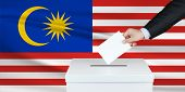 Election In Malaysia. The Hand Of Man Putting His Vote In The Ballot Box. Waved Malaysia Flag On Bac poster