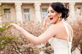 Happy beautiful bride dancing in wedding dress outside