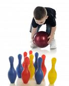 A tiny boy trying to roll a standard bowling ball to knock down his toy bowling pins.  Focus on boy and ball.  On a white background.