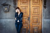 Sad Young Woman In Denim Clothing Standing Over Old Fashioned Historical Wooden Door, Rusty Postbox  poster