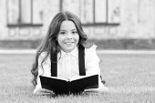Reading Is Passport To World. Happy Little Girl Enjoy Reading Book On Green Grass. Cute Small Child  poster