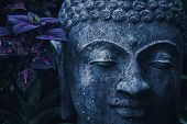 Stone Buddha Face Close-up In Trend Blue Color Toning. Handmade Carved Buddha Statue In Balinese Gar poster