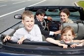 Family of four - parents and two children -  sits in a cabriolet, standing on the roadside, everybod